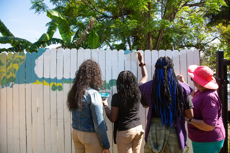 Students with THJCA paint a welcome sign inside the garden space, where they have their own garden plot.