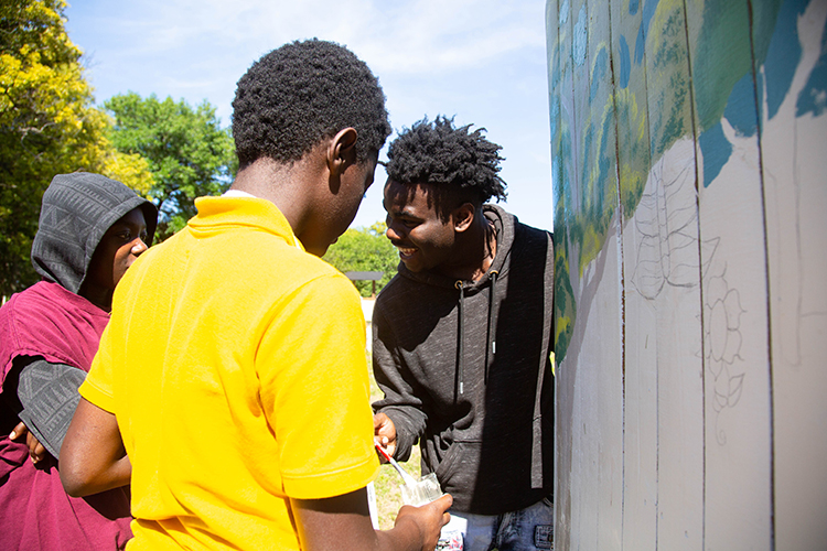 David Smith and his peers take turns painting at the Tampa Heights Community Garden.