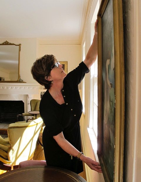 Kathy Gibson of Arthouse3 installing work in a client's home.