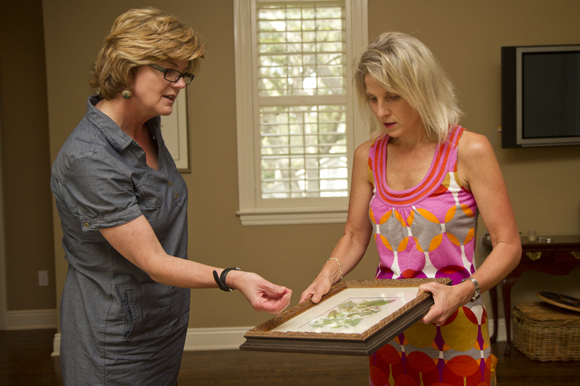 Katherine Gibson works with client Ashley Carl to install a few pieces of art.
