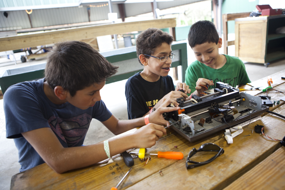 Friends (L-R) Tyler Visuvasam, Alejandro Acosta and Ian Pointer take apart a printer for fun. - Juli