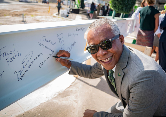 Calvin Williams, vice president for Administrative Services at USF, signs the 20-foot long, 800-pound beam placed on top of the new USF Health Morsani College of Medicine and Heart Institute.