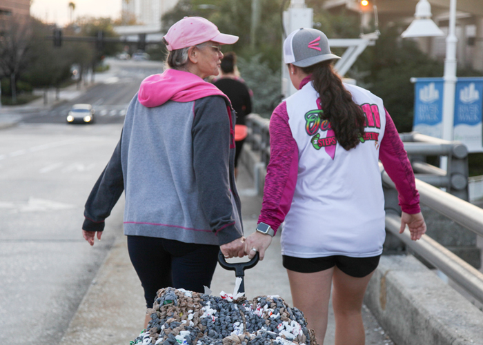 Sylvia Campbell, a breast cancer surgeon, and her daughter Meaghan Hoy pull a wagon of mats made from tied plastic bags to provide insulation from the ground.