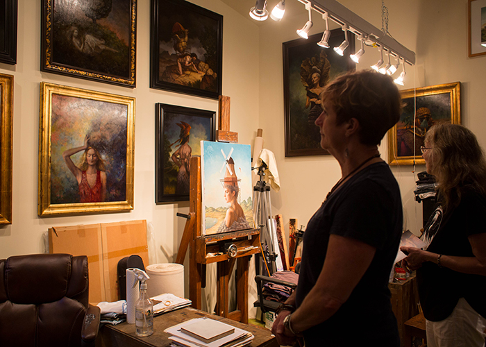 (L-R) Marty Bosy-Newlon and Kathy Barrera view oil paintings inside Steven Kenny's home studio.