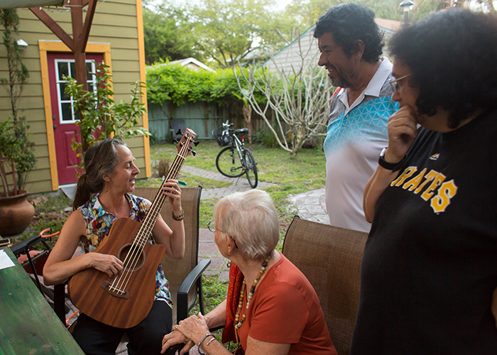 Diohn Brancaleoni plays tunes for AEHK members; Jan Richardson, Paul Barrera, and Annamarie Dotson, in her and her artist husband, Steven Kenny's backyard.
