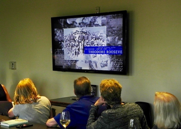 Pre-Launch Party-goers at Oxford Exchange watch a video trailer about 'Honoring the Enemy.'