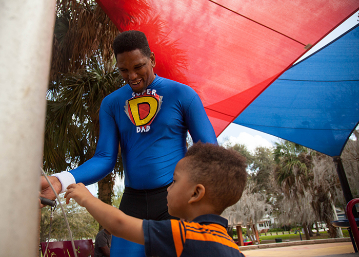 Maurice Vernon, aka Super Dad, plays with his son Dylan, age 2, at the Macfarlane Park where the 24M Dads 5K March will be held March 19th.
