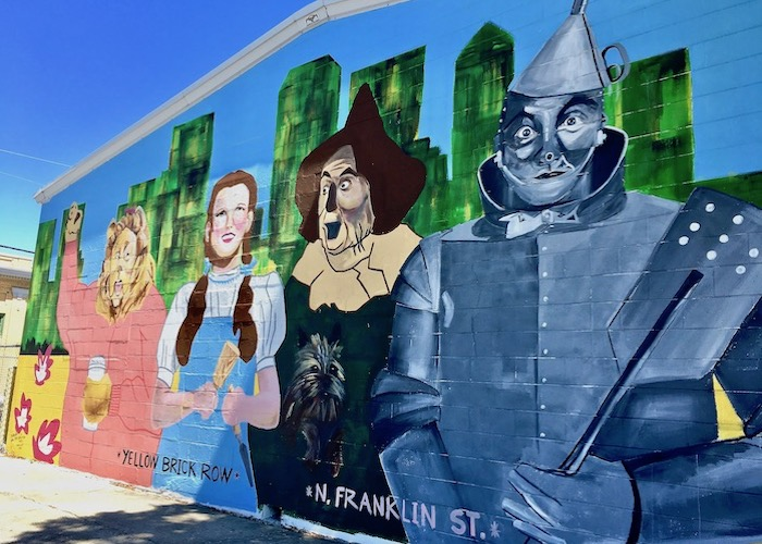 A whimsical mural depicts Yellow Brick Row in Tampa Heights.