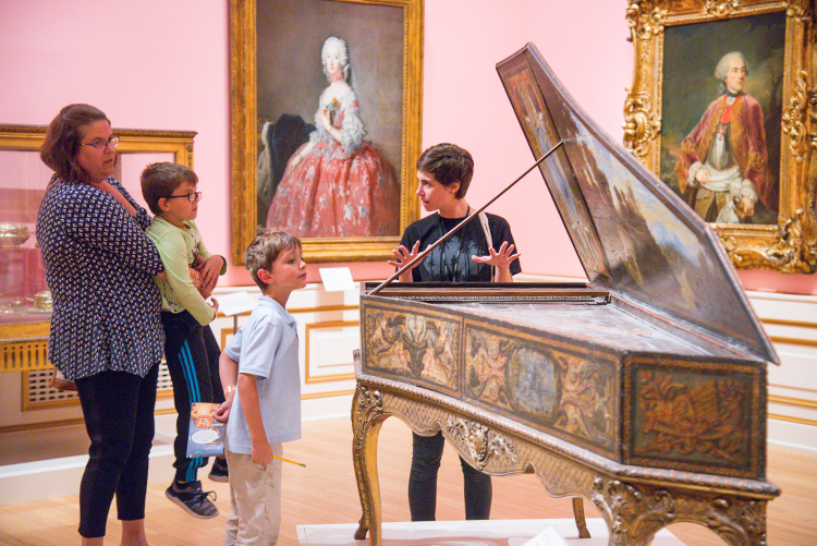 A family examines a harpsichord with a museum educator.