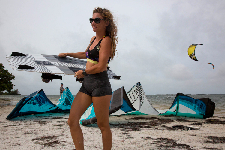 Rebecca Wilcox carries her board in after an early morning kite surf session.
