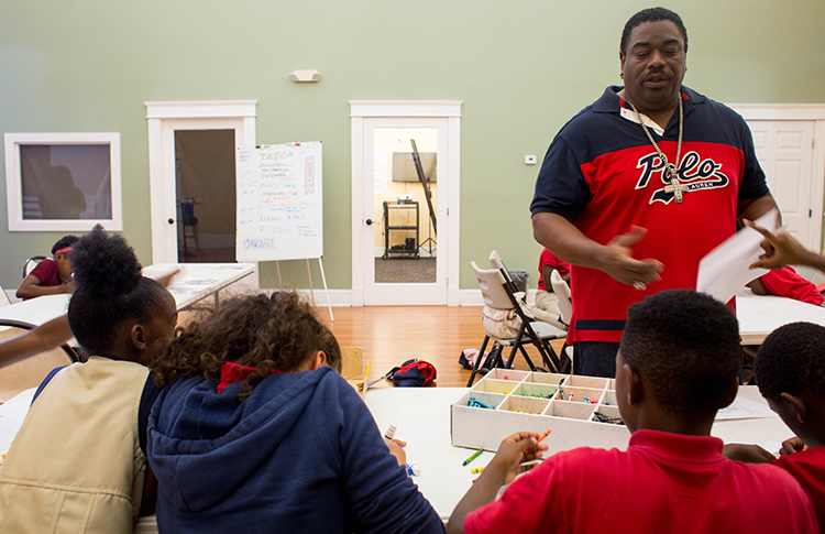Andrew Joseph, a facilitator with the young adult group at THJCA, greets students.
