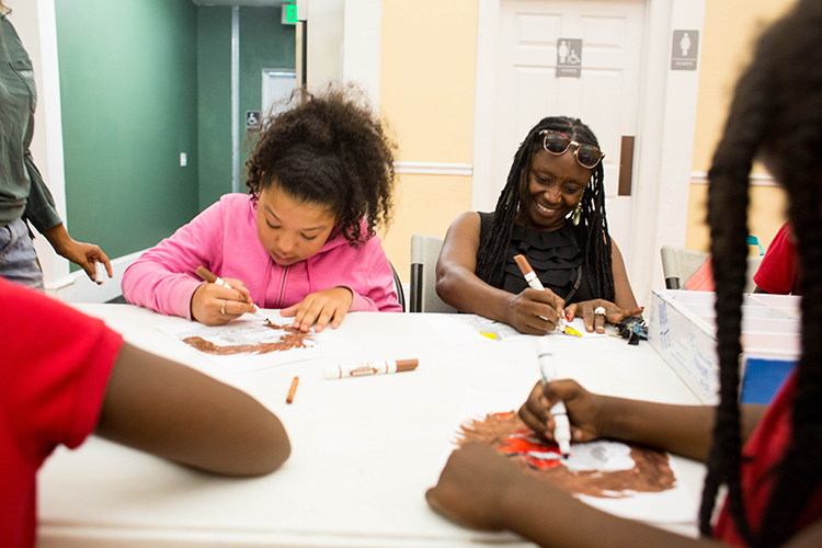Sonia Coleman works with students in an after-school program at the Tampa Heights Youth Development and Community Center.