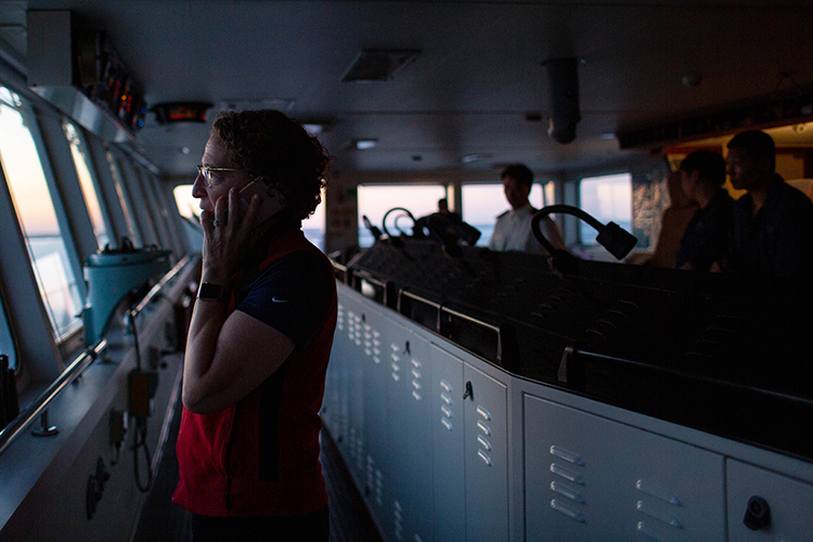 Harbor Pilot Carolyn Kurtz calls in tug boats to help slow the vessel as it brings in 3,000 shipping containers.