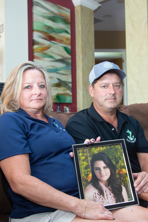 Lisa and Chris Acierno hold a picture of their daughter Hailey who died from suicide.