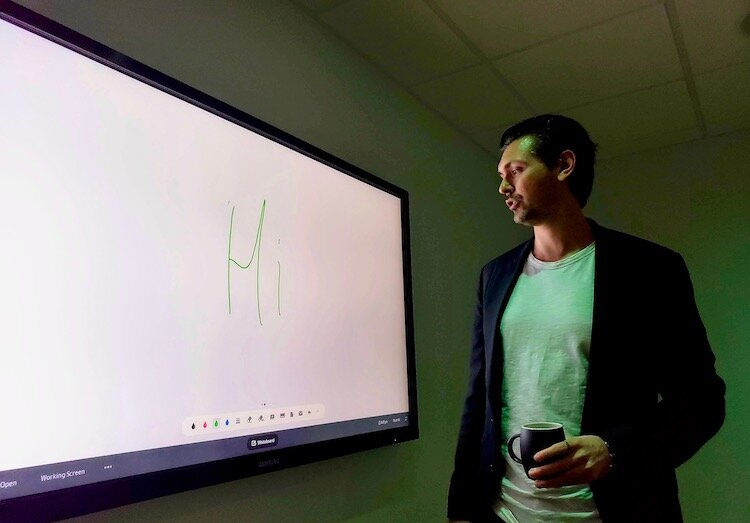 The Ring CEO Daniels Ikajevs demonstrates an electronic presentation panel in co-working space..