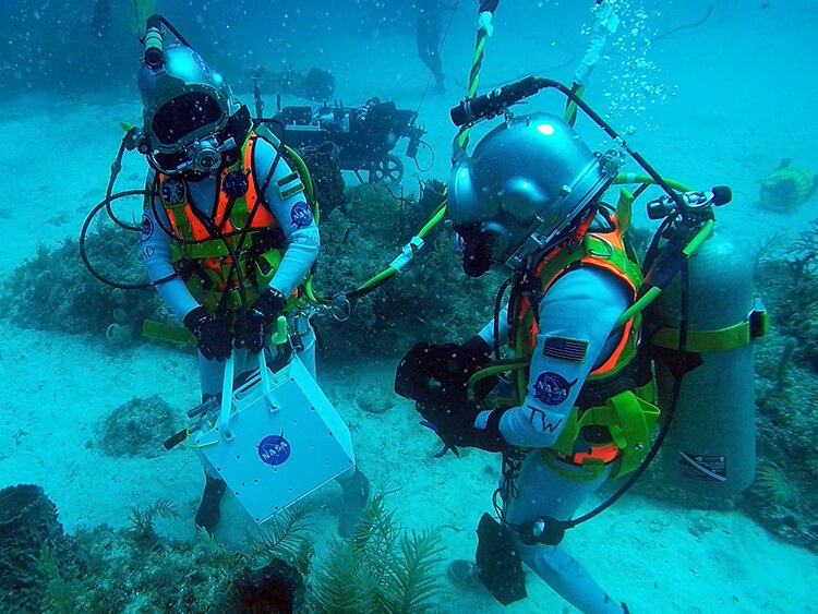 Researchers Csilla Ari D'Agostino and Samantha Cristoforetti leave the Aquarius habitat.