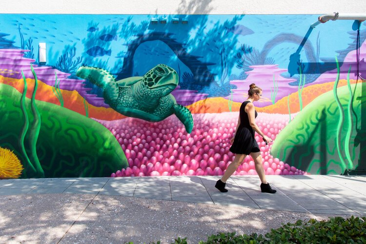 A woman passes mural art by Derek Donnelly who is known for his aquatic and coral scenes honoring his mentor BC Woo.