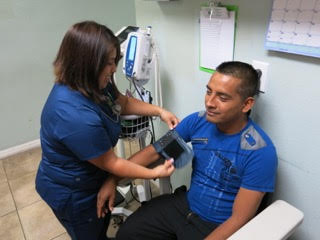 Carolina Galván, physician assistant, checks Gelacio Pacheco's vital signs at the Suncoast Community Health Center in Wimauma.