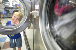 Archer Ayers, 1, plays at a Dunedin Coin Laundry with dad Dale close by. - Julie Branaman
