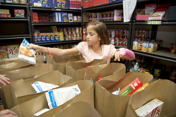 Lily Uline helps to assemble food bags at a food bank. - James Branaman