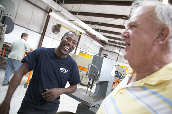 Welder Carlos Betts and CEO Dick Peck share a laugh.