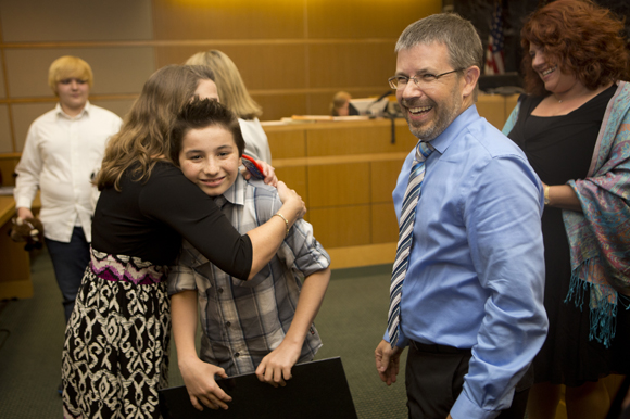 Mathew Kenty gets a hug from Heart Gallery's Tiffany Faykus.