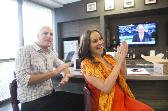 Chris Nelson and Kimberly Wacaser clap for coworker April Croswhite rings the office gong.