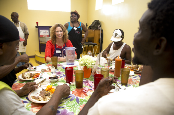 Mandy Cloninger sits and talks with Trinity Cafe guests as they have lunch.