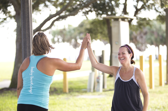 Christie Bruner and student Shelli Amow hi-five during Baby Boot Camp at Vinoy Park.