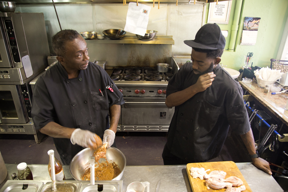 Chief's Creole Cafe Chef Carl McClellan shows Lorenza Jackson a recipe.
