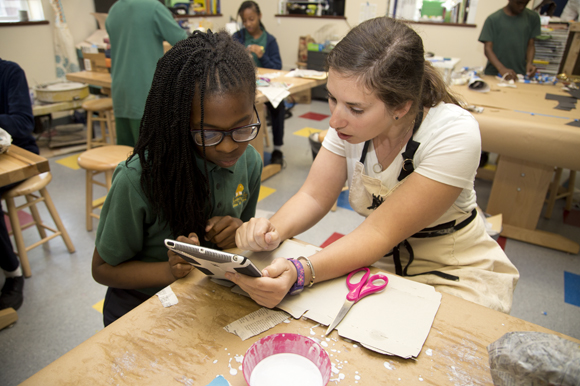 Academy Prep teach Amanda Fleishbein helps Jazmyn Wajd design her entry for the DooDad Competition.