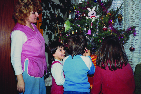 Karolak (the child at left) decorates a Christmas tree in Croatia with her cousins in 1987.