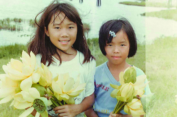 Water lilies found near a bridge delight Phuong, right, and her sister.