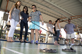 Bonnie Walker (R) teaches Kelly Clark and Megan Body the rules of shuffleboard at realize Bradenton's PopUps for a Purpose event.