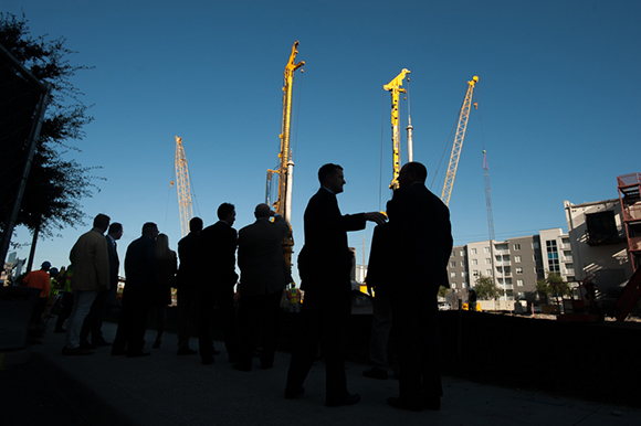 Officials gather near working cranes at the site of the upcoming Channel Club and Publix development in Channelside Friday morning. The group was there for a ceremonial groundbreaking for the media and other onlookers. Tampa Mayor Bob Buckhorn was on