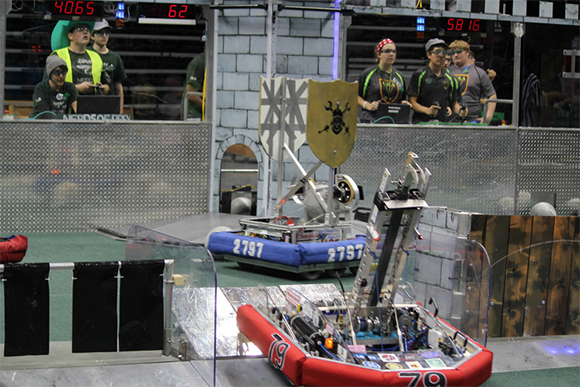 FIRST Robotics Competition robots negotiate defenses in the FIRST Stronghold game
