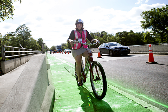 Founder & Principal, Pedal Power Promoters, Christine Acosta bikes the new green on Bullard Parkway.