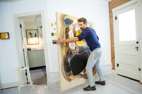 Artist Edgar Sanchez Cumbas packs up an installed painting for a client.