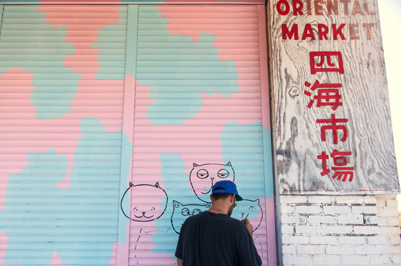 Cory Robinson adds color to wall space outside Cafe Hey and an Asian grocery store.