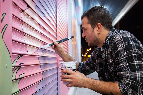 Charles Gallagher paints his first mural outside Cafe Hey and Oceanic Restaurant Equipment.