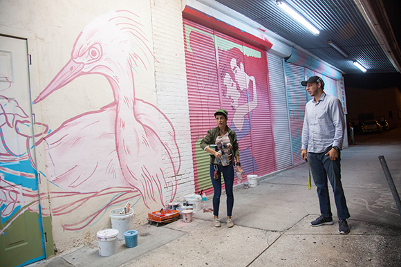 Michelle Sawyer preps to paint as Daniel Wind checks out the new evolving street art scape.