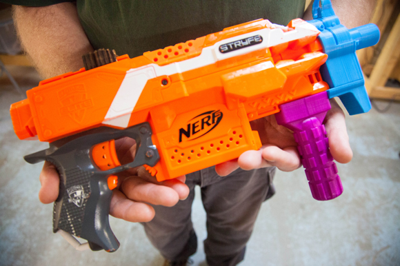 Bryan Lee holds a toy gun he made using a 3-D printer inside the 'Gym for Nerds' at Hackerspace.