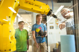 Ken Leung and Ben Faehn learn to program a robot from Professor Ron Smith at HCC.