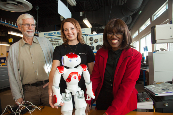 Ron Smith, Heather Canipe, and Shirley Dobbins with a humanoid used to teach students programming.