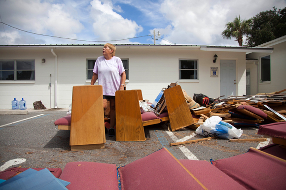 Ann Harrison stands amongst wreckage lost in the storm surge brought by Hurricane Hermine.