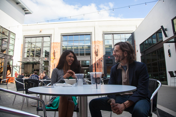 Juhi Kore and Jason Busto take a lunch break in the courtyard during opening day at Armature Works.