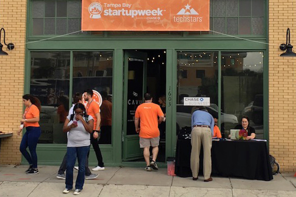 A steady flow of attendees enters and exits CAVU during Tampa Bay Startup Week.
