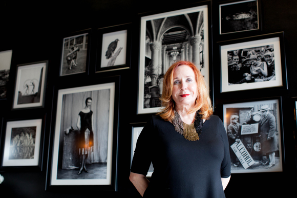 Carolyn Wilson, aka CW, stands in front of vintage photos at the entrance of CW's Gin Joint.