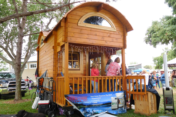 A tiny log cabin built by Unforgettable Tiny House displayed at the St. Pete Tiny Home Festival.