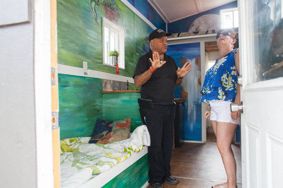 Mike Chretien with the St. Pete Eco Village shows Isabella Meade one of their tiny homes.